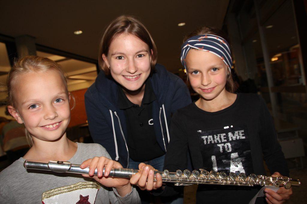 Anna Schulte (Mitte) aus dem Jugendorchester zeigt den Zwillingen Pia und Inga Sassenberg (beide 8) wie man eine Querflöte hält und ihr Töne entlockt