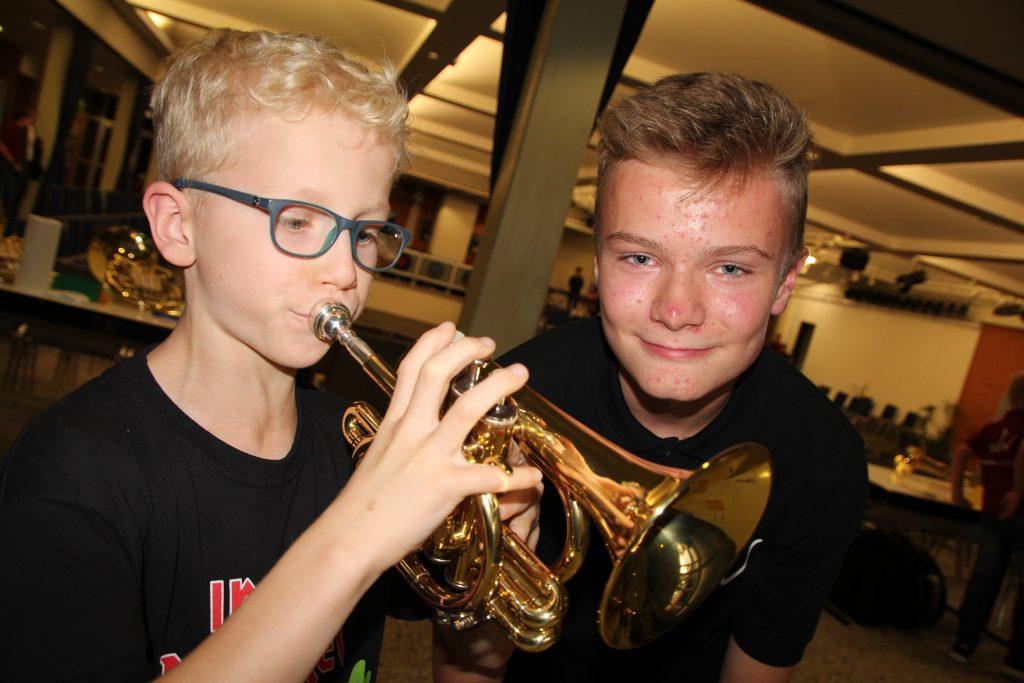 Ole Stammeier (links, 8) darf eine Pockettrompete ausprobieren. Louis Dreismickenbecker aus dem Schülerorchester hilft ihm dabei